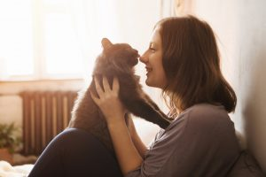 young woman plays with cat